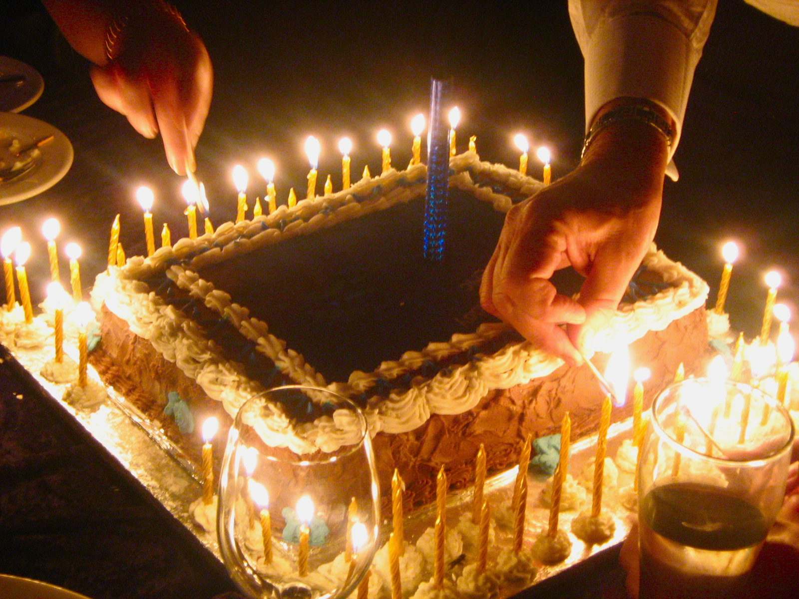 lighting candles on a cake for a 60th birthday celebration & birthday party