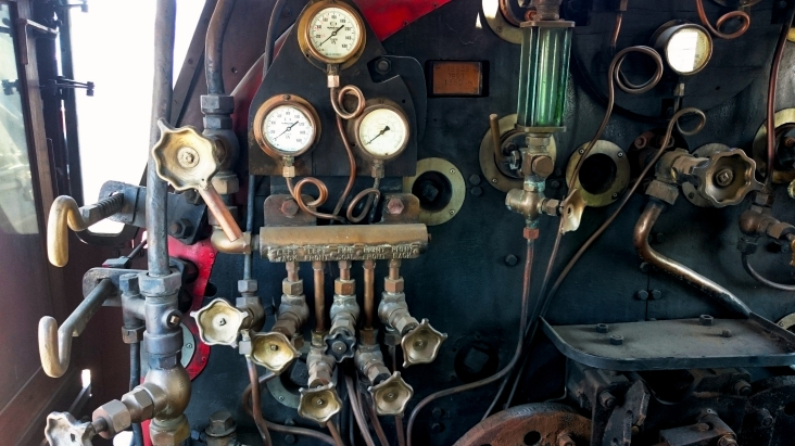 dials and valves in the cab of a steam locomotive