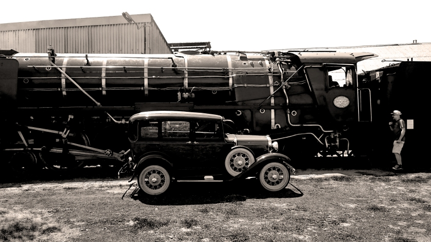1931 model a ford poses next to a steam locomotive